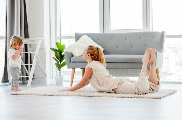 Красивая девушка-мать тренируется со своим маленьким сыном в комнате с красивым скандинавским интерьером