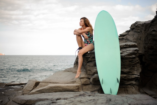 Beautiful girl in the multi colored swimsuit sitting near the surfboard on the rock over the atlantic ocean and clear sky