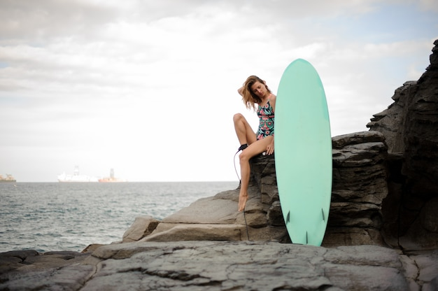 Beautiful girl in the multi colored swimsuit sitting with the surfboard on the rock over the atlantic ocean and clear sky