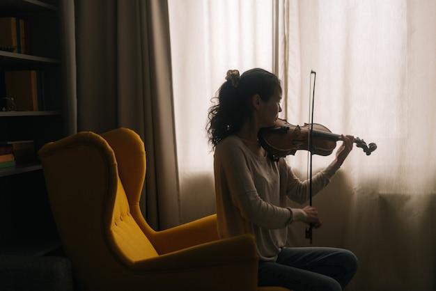 Красивая девушка музыкант играет на фоне окна дома, сидя на мягком стуле