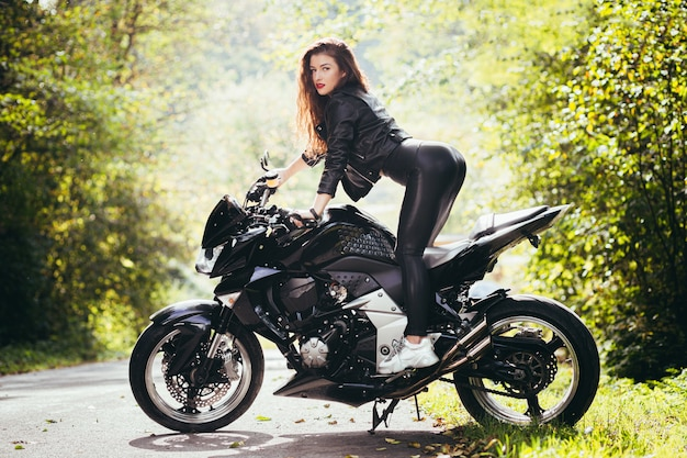 Beautiful girl near the black motorcycle, portrait, in the woods near the road, autumn