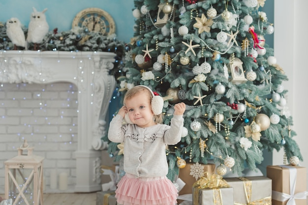 Beautiful girl near decorated christmas tree with toy wooden rocking horse. happy new year. portrait little girl.
