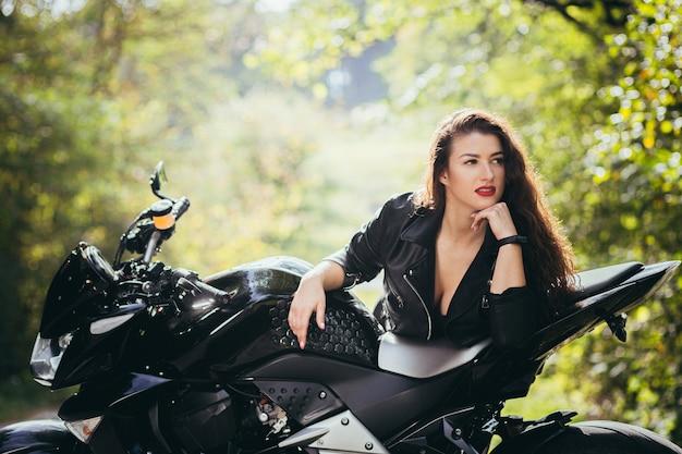 Красивая девушка возле черного мотоцикла, портрет, в лесу у дороги, осень