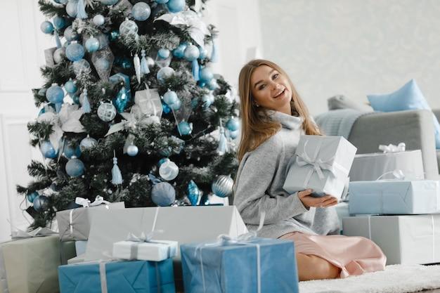 Красивая девушка возле елки в окружении подарков, распаковывает подарки