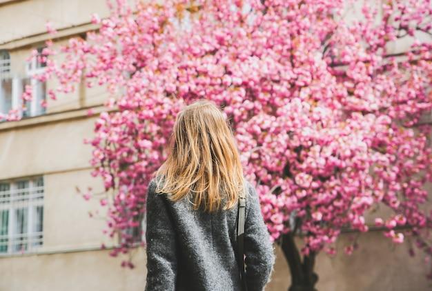 Красивая девушка возле деревьев сакуры. женщина в платье и стильном пальто в ужгороде цветут розовые цветы. цветут вокруг. весеннее время. концепция расслабления и счастья.
