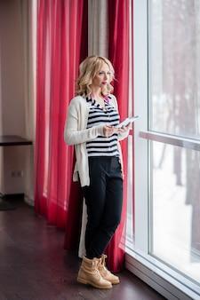 Красивая девушка у окна, блондинка, ноутбук