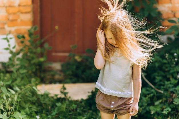 風から髪を上げたドアの横にある美しい少女
