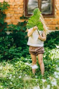 彼女の手で葉を持つ壁の横にある美しい少女