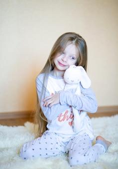긴 금발 머리와 파란 눈을 가진 8 세의 아름다운 소녀가 방의 푹신한 카펫에 잠옷에 앉아 부드럽게 장난감 토끼를 안아줍니다.