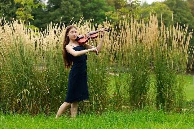 Красивая девушка азиатской внешности со скрипкой в парке. фото высокого качества