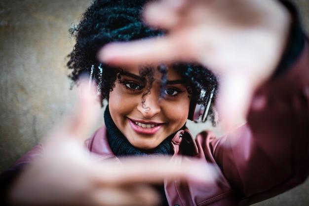 黒人の美少女が大きな白いヘッドホンで音楽を聴きます。
