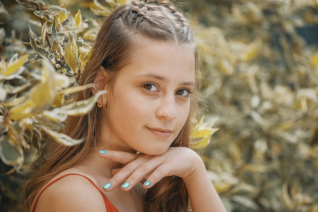 葉の背景に美しい少女。クローズアップポートレート