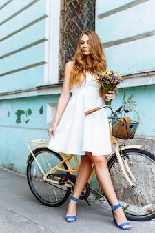 Красивая девушка на велосипеде возле старинного здания Premium Фотографии