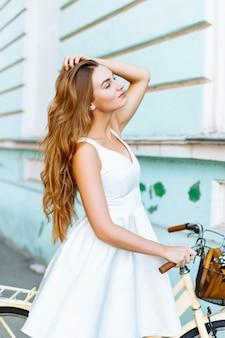 Красивая девушка на велосипеде возле старинного здания