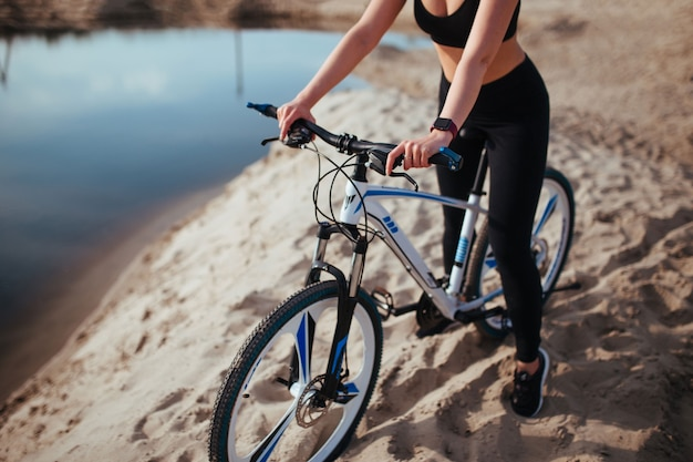 강 근처 모래에 자전거에 아름 다운 소녀