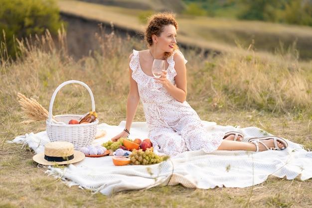 絵のように美しい場所でのピクニックの美しい少女。ロマンチックなピクニック。