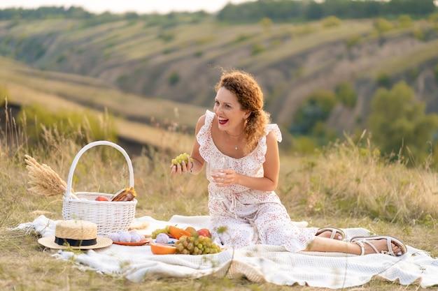 絵のように美しい場所でのピクニックの美しい少女。