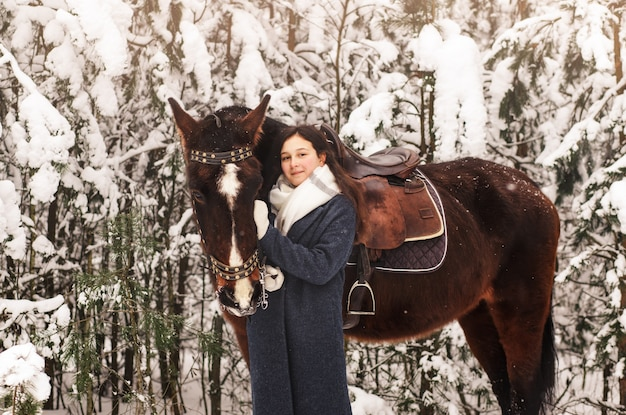 森の中で冬に馬と散歩の美しい少女