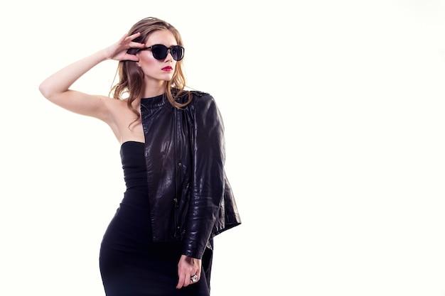 Красивая девушка на белом фоне в черном платье и кожаной куртке с очками