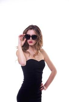 Красивая девушка на белом фоне в черном платье с очками