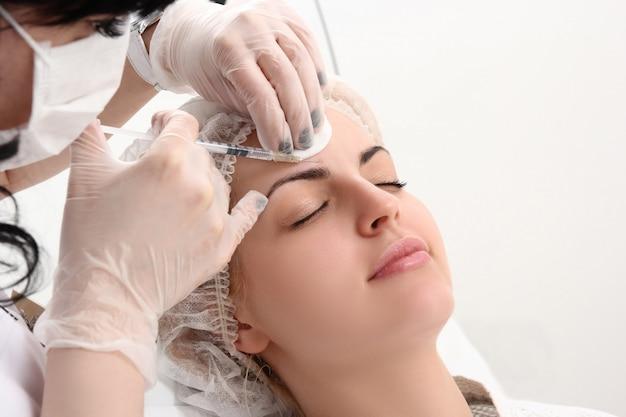Красивая девушка на процедуре омоложения в клинике красоты