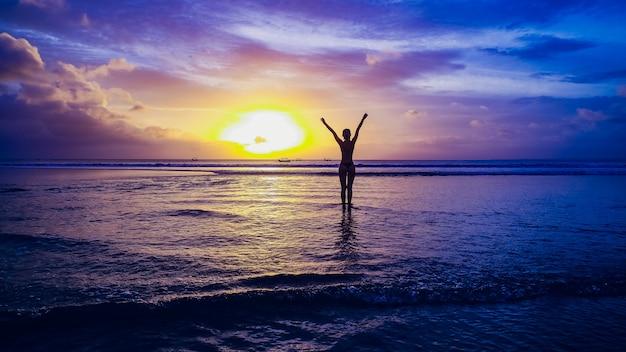 Красивая девушка на фоне заката на песчаном пляже