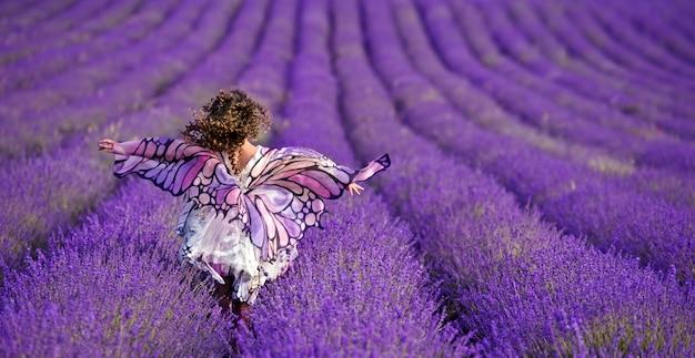 라벤더 밭에 아름 다운 소녀입니다. 곱슬 머리를 가진 여자입니다. 나비