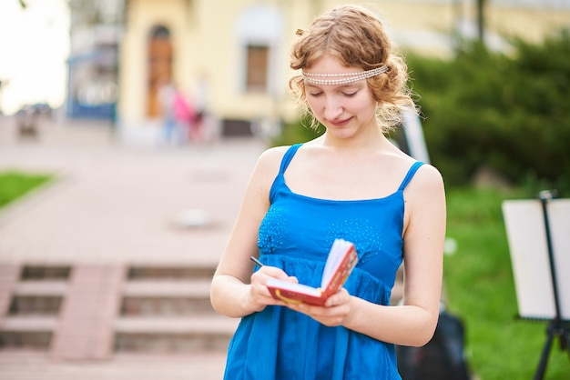あらゆる目的のためにノートブックに何かを書いている青いドレスを着た通りの美しい少女