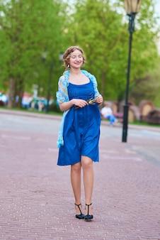 彼女の手でタッセルを持って通りを歩いている青いドレスを着た通りの美しい少女