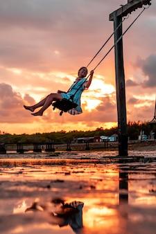 일몰 발리 인도네시아에서 나무 그네에 아름 다운 소녀