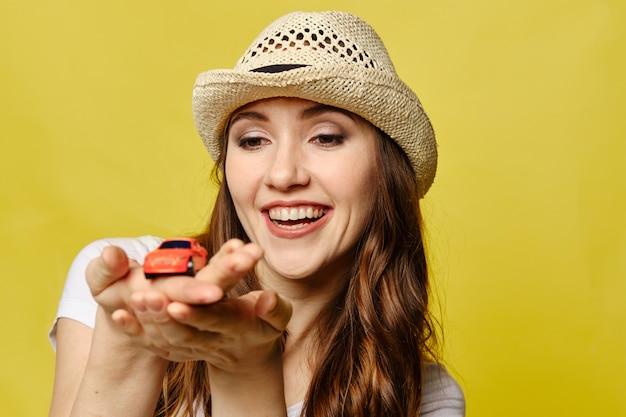 黄色の美しい少女は、車での旅行の概念として手のひらにおもちゃの車を見てください。