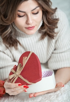 Beautiful girl open red heart gift box. valentine's day concept