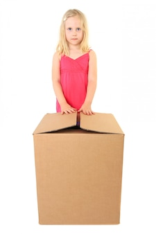 Beautiful girl opens a large cardboard box with a copy space for text