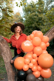 A beautiful girl in an orange shirt, a black skirt and a witch hat. laughs. halloween