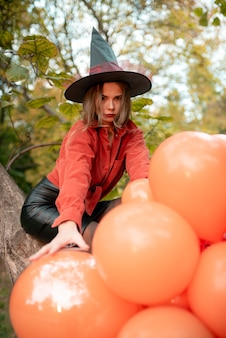 Beautiful girl in an orange shirt, black skirt and witch hat. looks into the camera. halloween