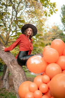 Beautiful girl in an orange shirt, black skirt and witch hat. sits in a tree. halloween