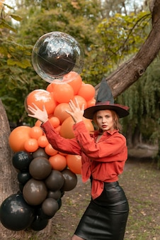 Beautiful girl in an orange shirt, black skirt and witch hat. will throw up a balloon. halloween