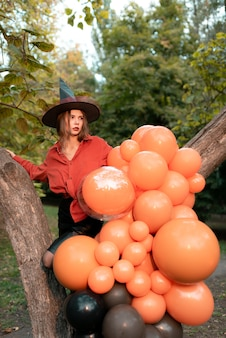 A beautiful girl in an orange shirt, a black skirt and a witch's hat. she looks to the side. halloween
