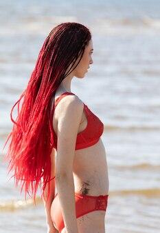 야외에서 자연을 즐기는 아름 다운 소녀. 붉은 수영복을 입은 주홍색 향취를 가진 반나체 소녀가 해변에서 일광욕을 하고 있다