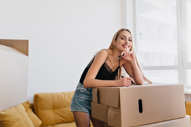Beautiful girl packing stuff, labeling cardboard box, holding marker in hand, moving to new apartment, flat, house. smiling woman in room with yellow sofa, she wearing denim shorts, black top.