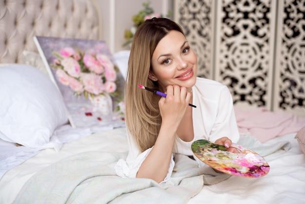 Красивая девушка-живописец на кровати в своей комнате восхищается картиной, которую она нарисовала