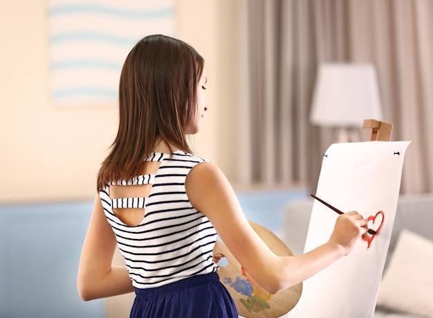 部屋のキャンバスに絵を描く美しい少女