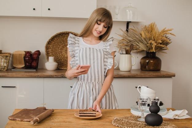Красивая девушка кондитер или домохозяйка делает фото десерта по телефону