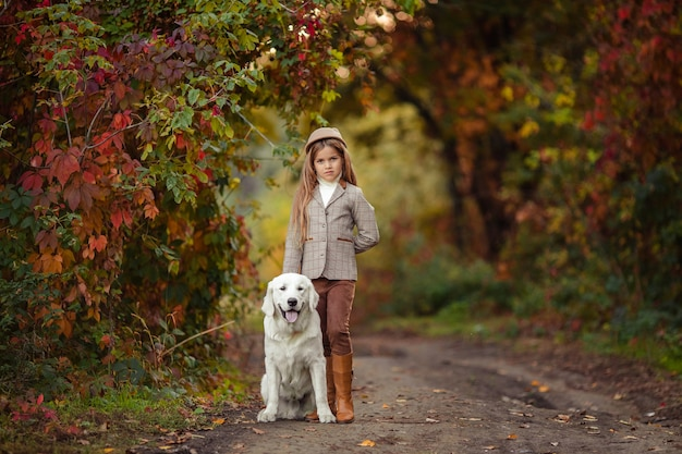 A beautiful girl and a pet retriever for a walk in the autumn park