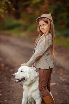 Beautiful girl and a pet retriever for a walk in the autumn park