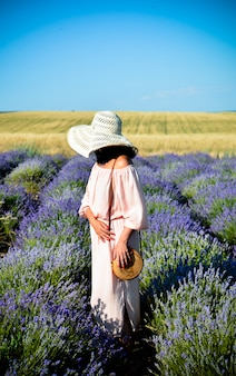 Beautiful girl in a pink dress and black hat in a lavender field