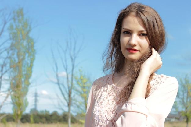 Beautiful girl in a pink dress in field.