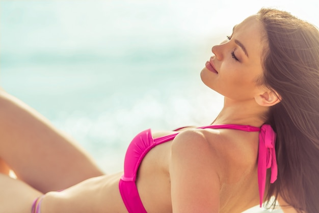 Beautiful girl in pink swimsuit is lying with closed eyes.