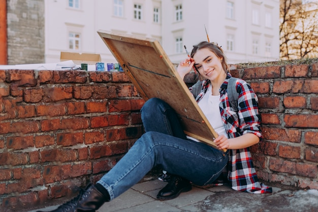 Beautiful girl in a plaid shirt draws old buildings while sitting near a brick wall.