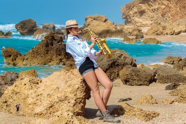 Красивая девушка играет на саксофоне на берегу моря.